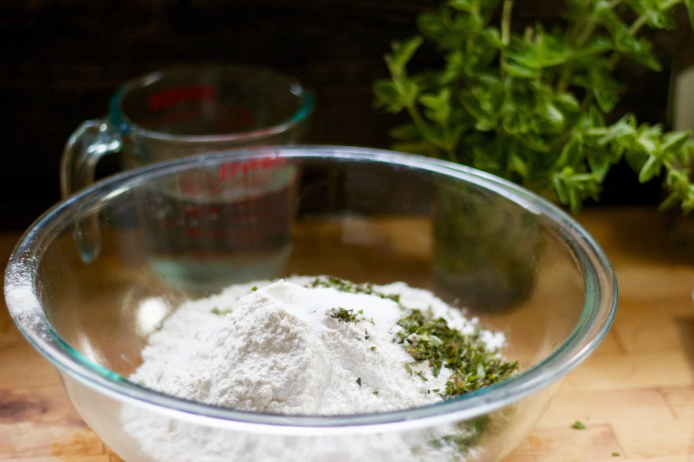 Mixing up bread dough with oregano